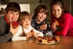 Niños que gozan de la placa de tortas en cocina Imagenes de archivo
