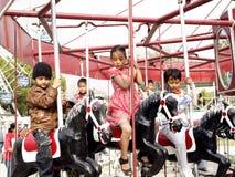 Niños que gozan ?del carrusel del caballo de vuelo? Fotografía de archivo
