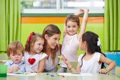 Niños que hablan con el profesor del cuarto de niños Imagenes de archivo