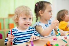 Niños que hacen artes y artes en centro de cuidado de día juntos Imagenes de archivo