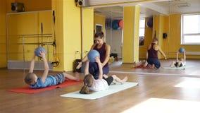 Niños que hacen ejercicio con las bolas médicas