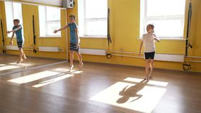Niños que hacen ejercicios físicos en gimnasio almacen de metraje de vídeo