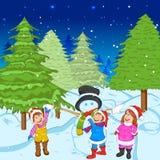 Niños que hacen el muñeco de nieve durante la Navidad santa Imagen de archivo