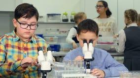 Niños que hacen experimentos científicos en la clase de Biología de la escuela Mirada en un microscopio metrajes