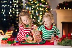 Niños que hacen la casa del pan del jengibre de la Navidad Fotografía de archivo libre de regalías