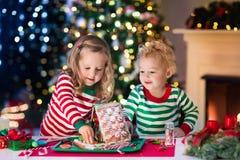 Niños que hacen la casa del pan del jengibre de la Navidad Fotografía de archivo