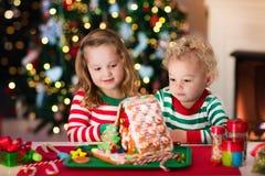 Niños que hacen la casa del pan del jengibre de la Navidad Imagen de archivo libre de regalías