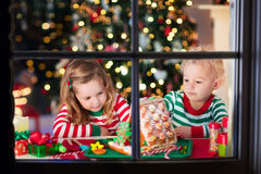 Niños que hacen la casa del pan del jengibre de la Navidad Foto de archivo