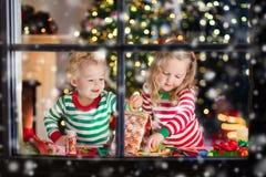 Niños que hacen la casa del pan del jengibre de la Navidad Imagenes de archivo