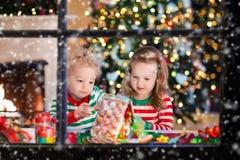 Niños que hacen la casa del pan del jengibre de la Navidad Fotos de archivo