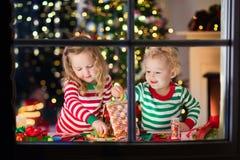 Niños que hacen la casa del pan del jengibre de la Navidad Foto de archivo libre de regalías