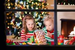 Niños que hacen la casa del pan del jengibre de la Navidad Imágenes de archivo libres de regalías