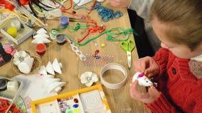 Niños que hacen la decoración para los días de fiesta, artes y juguetes, árbol de navidad y otro metrajes