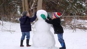 Niños que hacen un muñeco de nieve almacen de video