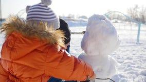 Niños que hacen un muñeco de nieve en el patio metrajes
