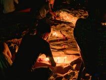 Niños que iluminan velas en la arena en la playa Fotos de archivo