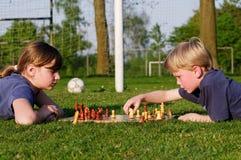 Niños que juegan a ajedrez en un campo de fútbol Fotos de archivo libres de regalías