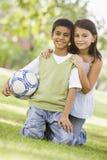 Niños que juegan al balompié en parque Imagen de archivo