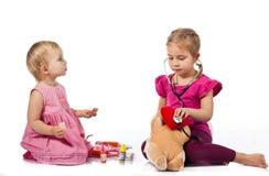 Niños que juegan al doctor con una muñeca Imágenes de archivo libres de regalías