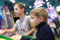 Niños que juegan al juego de arcada imágenes de archivo libres de regalías