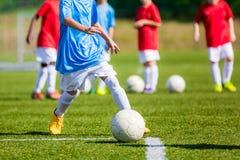 Niños que juegan al juego de fútbol en el campo de fútbol profesional Imágenes de archivo libres de regalías