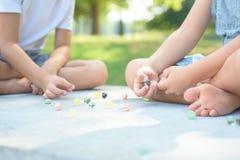 Niños que juegan al juego de los mármoles afuera Fotos de archivo libres de regalías