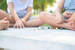 Niños que juegan al juego de los mármoles afuera Imagen de archivo libre de regalías