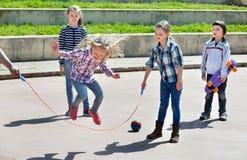 Niños que juegan al juego de salto de la cuerda que salta Imágenes de archivo libres de regalías