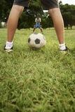 Niños que juegan al juego del fútbol y de fútbol en parque fotos de archivo