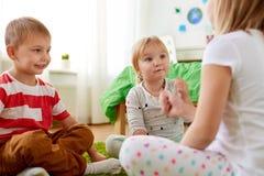 Niños que juegan al juego del piedra papel o tijera en casa imagenes de archivo