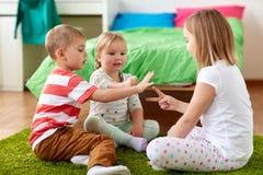 Niños que juegan al juego del piedra papel o tijera en casa fotos de archivo libres de regalías