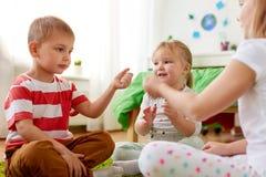 Niños que juegan al juego del piedra papel o tijera en casa fotos de archivo