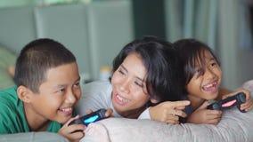 Niños que juegan al videojuego con su madre almacen de video