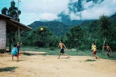 niños que juegan alto del fútbol para arriba en las montañas en el medio del bosque de la nube imagen de archivo libre de regalías