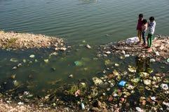 Niños que juegan cerca de sucio dejado en desorden con la ruina del lago, mirando los pescados imágenes de archivo libres de regalías