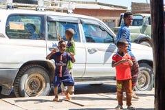 Niños que juegan cerca de un coche de los turistas foto de archivo