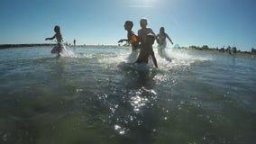 Niños que juegan con el arma de agua de la playa almacen de video