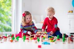 Niños que juegan con el ferrocarril y el tren del juguete Fotografía de archivo libre de regalías