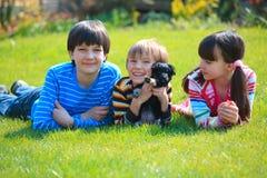 Niños que juegan con el perro Imágenes de archivo libres de regalías