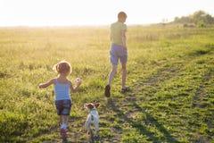 Niños que juegan con el perro en la puesta del sol, Fotos de archivo libres de regalías
