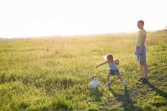 Niños que juegan con el perro en la puesta del sol, Foto de archivo libre de regalías
