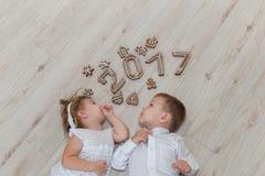 Niños que juegan con el ` s Eve del Año Nuevo del pan de jengibre Imagenes de archivo