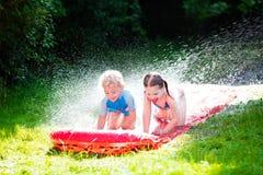 Niños que juegan con el tobogán acuático del jardín Imagen de archivo