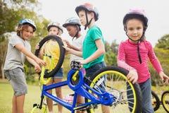 Niños que juegan con la bici en el parque Imágenes de archivo libres de regalías