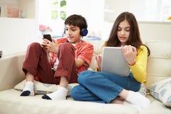 Niños que juegan con la tableta de Digitaces y el MP3 Fotos de archivo libres de regalías