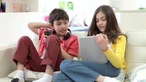 Niños que juegan con la tableta y el reproductor Mp3 de Digitaces almacen de metraje de vídeo
