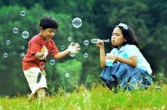 Niños que juegan con las burbujas de jabón Fotos de archivo libres de regalías