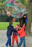Niños que juegan con las burbujas de jabón en Londres Imágenes de archivo libres de regalías