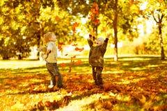 Niños que juegan con las hojas caidas otoño en parque Imágenes de archivo libres de regalías