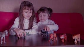 Niños que juegan con los animales del juguete almacen de metraje de vídeo